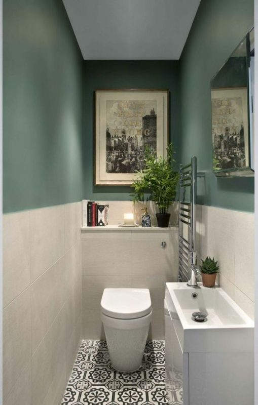 a-small-and-stylish-guest-toilet-with-green-and-white-tile-walls-a-sink-with-a-vanity-for-storage-and-some-artworks